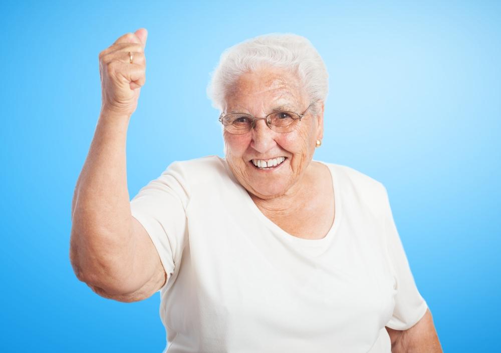 portrait of old woman doing a winner gesture